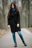 La muchacha hermosa joven en una capa negra y la bufanda azul para un paseo en el otoño/la primavera parquean Una muchacha morena Imagen de archivo libre de regalías