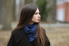 La muchacha hermosa joven en una capa negra y la bufanda azul para un paseo en el otoño/la primavera parquean Una muchacha morena Fotos de archivo libres de regalías
