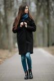 La muchacha hermosa joven en una capa negra y la bufanda azul para un paseo en el otoño/la primavera parquean Una muchacha morena Fotos de archivo