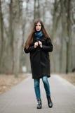 La muchacha hermosa joven en una capa negra y la bufanda azul para un paseo en el otoño/la primavera parquean Una muchacha morena Imagenes de archivo
