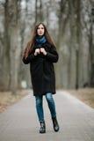 La muchacha hermosa joven en una capa negra y la bufanda azul para un paseo en el otoño/la primavera parquean Una muchacha morena Foto de archivo