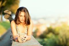 La muchacha hermosa joven en una pared en una ciudad envía el mensaje con soci Imagen de archivo libre de regalías