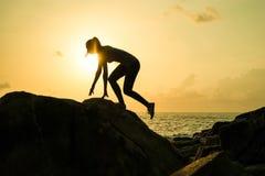 La muchacha hermosa joven la deportista, en zapatillas de deporte de la ropa de deportes salta a través de rocas en la puesta del Foto de archivo libre de regalías