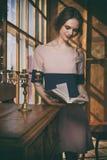 La muchacha hermosa joven lee el libro cerca de ventana Imagen de archivo