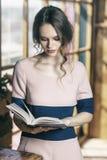 La muchacha hermosa joven lee el libro cerca de ventana imágenes de archivo libres de regalías