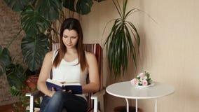 La muchacha hermosa joven lee el libro que se sienta en una silla La mujer busca algo en el libro almacen de video