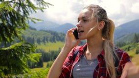 La muchacha hermosa joven llama por el teléfono móvil en las montañas almacen de video