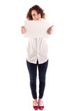 La muchacha hermosa joven lleva a cabo una muestra blanca vacía para que usted complete Imagen de archivo libre de regalías