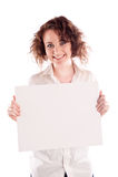La muchacha hermosa joven lleva a cabo una muestra blanca vacía para que usted complete Imagen de archivo