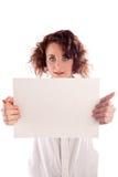 La muchacha hermosa joven lleva a cabo una muestra blanca vacía para que usted complete Imágenes de archivo libres de regalías