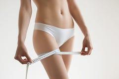 La muchacha hermosa joven mide a sus partes del cuerpo de la ruleta Imagen de archivo