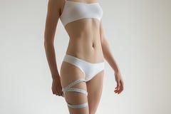 La muchacha hermosa joven mide a sus partes del cuerpo de la ruleta Imagen de archivo libre de regalías