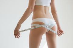 La muchacha hermosa joven mide a sus partes del cuerpo de la ruleta Foto de archivo libre de regalías