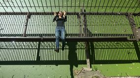 La muchacha hermosa joven miente y ríe en el puente oxidado del metal sobre el agua verde almacen de video