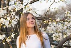 La muchacha hermosa joven mira para arriba en el fondo blanco de la magnolia Foto de archivo libre de regalías