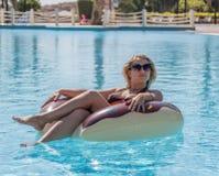 La muchacha hermosa joven nada en la piscina imagenes de archivo