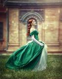La muchacha hermosa, joven, pelirroja en un vestido medieval verde, sube las escaleras al castillo Foto de archivo