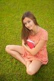 La muchacha hermosa joven que abraza un libro se sienta en la hierba verde Foto de archivo