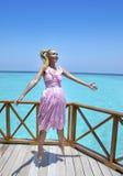 La muchacha hermosa joven salta en los sundress rosados en la plataforma del chalet en el agua debajo del paraguas, Maldivas fotografía de archivo