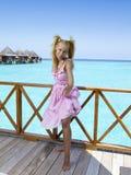 La muchacha hermosa joven se coloca en los sundress rosados en el sundeck del chalet en el agua, Maldivas fotos de archivo