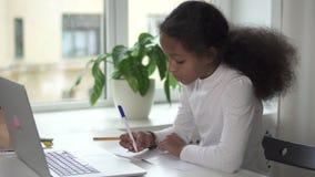La muchacha hermosa joven se está sentando en la tabla y está haciendo la preparación usando el nuevo ordenador portátil moderno  almacen de metraje de vídeo