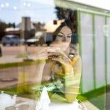 La muchacha hermosa joven se sienta en el café, día soleado, sosteniendo una taza, estilo de la moda Foto de archivo libre de regalías