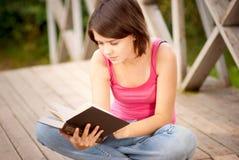 La muchacha hermosa joven se sienta en el puente y lee el libro Imagenes de archivo