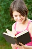La muchacha hermosa joven se sienta en el puente y lee el libro Fotos de archivo libres de regalías