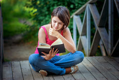 La muchacha hermosa joven se sienta en el puente y lee el libro Fotografía de archivo libre de regalías