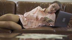 La muchacha hermosa joven se sienta en el sofá de cuero que habla por el teléfono móvil, mirando el ordenador y contando efectivo almacen de metraje de vídeo
