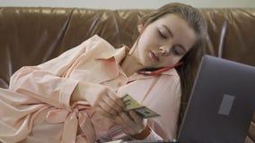 La muchacha hermosa joven se sienta en el sof? de cuero que habla por el tel?fono m?vil, mirando el ordenador y contando efectivo almacen de metraje de vídeo
