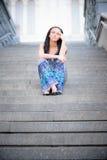 La muchacha hermosa joven se sienta en pasos de progresión Imagen de archivo libre de regalías