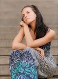 La muchacha hermosa joven se sienta en pasos de progresión Fotos de archivo