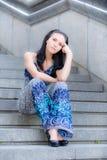 La muchacha hermosa joven se sienta en pasos de progresión Imágenes de archivo libres de regalías