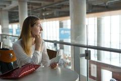 La muchacha hermosa joven se sienta en la tabla con el boleto y espera el aeroplano fotografía de archivo