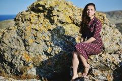 La muchacha hermosa joven se sienta en una piedra, mirada tranquila recta Emotio Foto de archivo