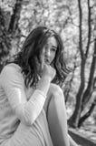 La muchacha hermosa joven sienta triste en un vestido blanco en una calle en la ciudad de la primavera de Lviv Imágenes de archivo libres de regalías