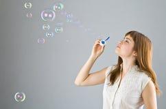 La muchacha hermosa joven sopla hacia fuera burbujas de jabón Foto de archivo