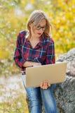 La muchacha hermosa joven sostiene un ordenador portátil en sus manos, sentándose en Imagenes de archivo