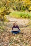 La muchacha hermosa joven sostiene un ordenador portátil en sus manos, sentándose en fal Imagen de archivo libre de regalías