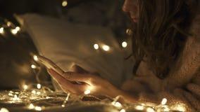 La muchacha hermosa joven utiliza el teléfono rodeado con las luces del bokeh Mujer morena de los pelos rizados Sitio de la decor metrajes