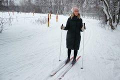 La muchacha hermosa joven va a esquiar en la estación del invierno en un primer de la cuesta del esquí Imagenes de archivo