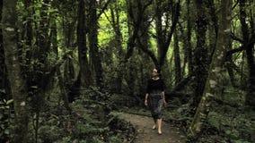 la muchacha hermosa 4k en falda hecha a mano negra ajusta las texturas, desfiladero en una manera de madera profundamente en el b almacen de video