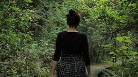 la muchacha hermosa 4k en falda hecha a mano negra ajusta las texturas, desfiladero en una manera de madera profundamente en el b almacen de metraje de vídeo