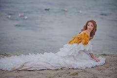 La muchacha hermosa le gusta un cisne en la playa Imagen de archivo