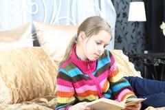 La muchacha hermosa lee el compartimiento Fotografía de archivo