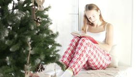 La muchacha hermosa lee el libro del Año Nuevo Ella se sienta por la ventana grande metrajes