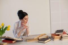 La muchacha hermosa lee los libros en la tabla que se prepara para el examen Fotografía de archivo libre de regalías