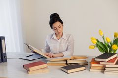 La muchacha hermosa lee los libros en la tabla que se prepara para el examen Imagen de archivo libre de regalías