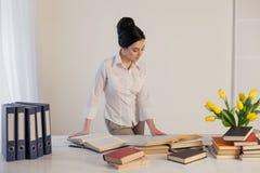La muchacha hermosa lee los libros en la tabla que se prepara para el examen Foto de archivo